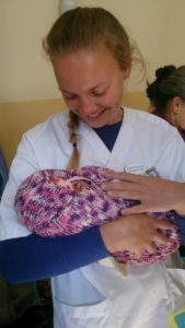 Ingrid med en baby tullet inn i teppet som hun har strikket.